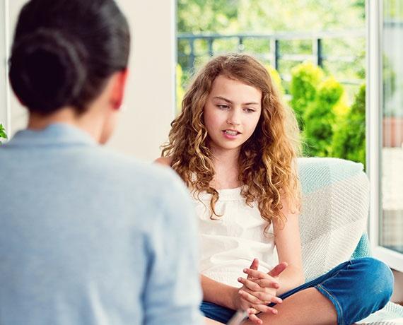 Das Bild zeigt ein jungens Mädchen mit der Mutter, welche ein Gespräch führen.