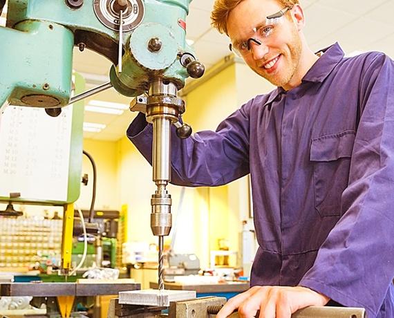 Das Bild zeigt einen jungen Mann, welcher mit einer großen Bohrmaschine ein Loch in das Werkstück bohrt.