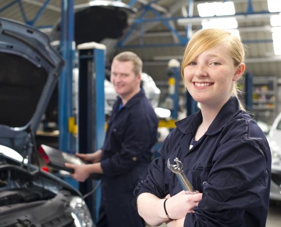 Zwei junge Menschen bei der Arbeit an einem Auto.
