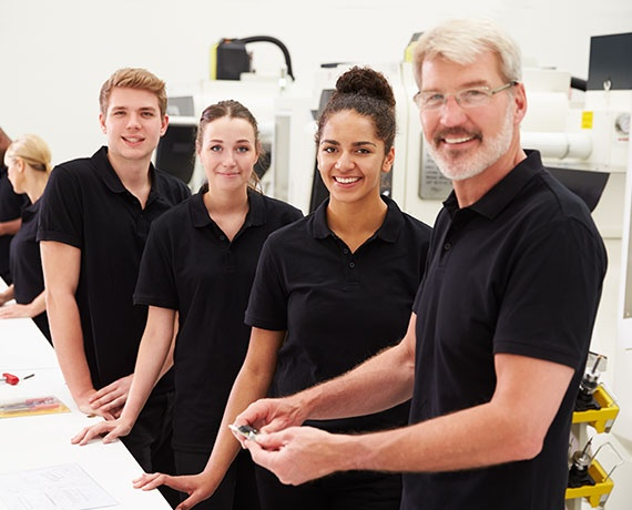 Das Bild zeigt drei Jugendliche und Erwachsenen bei der Arbeit.