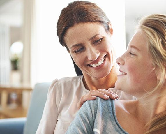 Das Bild zeigt Mutter und Tochter, welche sich lächelnd ansehen.