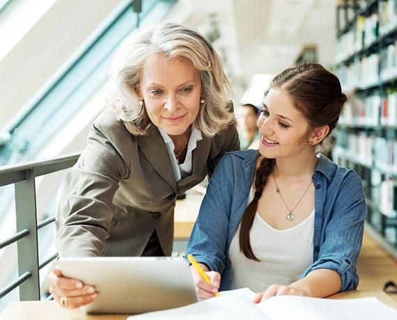 Das Bild zeigt eine Schülerin und eine Lehrerin, gemeinsam in der Bibliothek.