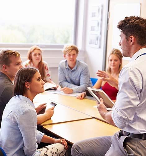 Das Bild zeigt fünf SchülerInnen und Erwachsenen der einen Vortrag vor den SchülerInnen halt.