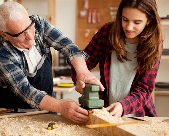 Das Bild zeigt ein Mädchen und einen Mann. Sie arbeiten gemeinsam an einem Holzstück.
