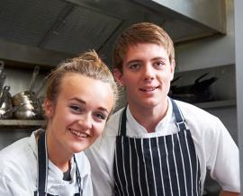 Das Bild zeigt ein Mädchen und einen Jungen im Kochgewand.