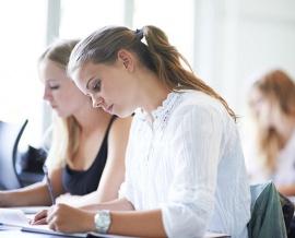 Das Bild zeigt drei Mädchen, welche in der Schule sitzen und im Unterricht mitschreiben.