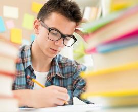 Das Bild zeigt einen konzentrierten jungen Mann bei den Hausaufgaben.