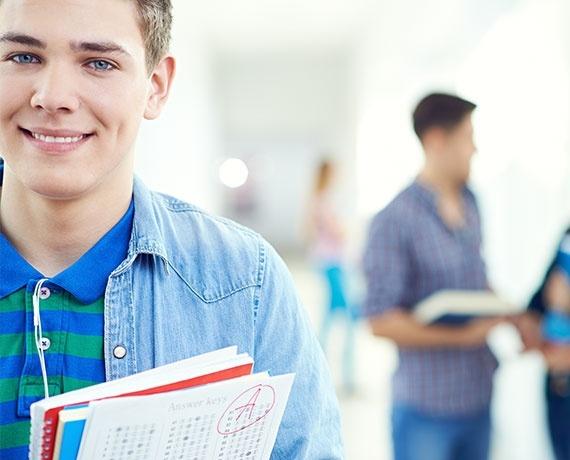 Das Bild zeigt einen lächelden jungen Mann mit Schulunterlagen in der Hand.