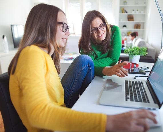 Das Bild zeigt Mutter und Tochter, welche gemeinsam vor dem Laptop sitzen.
