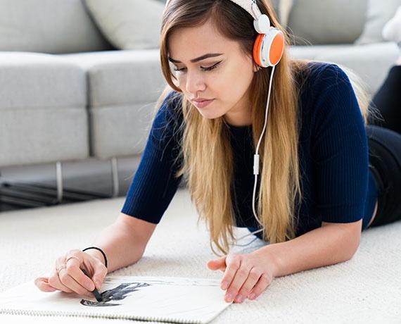 Das Bild zeigt ein jugendliches Mädchen, welches auf dem Boden liegt, dabei malt und Musik hört.
