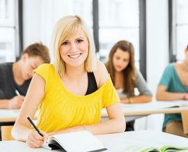 Das Bild zeigt ein lächelndes Mädchen in der Schule. Im Hintergrund sind drei weitere SchülerInnen.