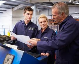 Das Bild zeigt zwei Jugendliche und einen Erwachsenen, welcher die Arbeit auf einem Plan erklärt.
