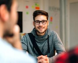 Das Bild zeigt einen jungen Mann bei einem Bewerbungsgespräch.