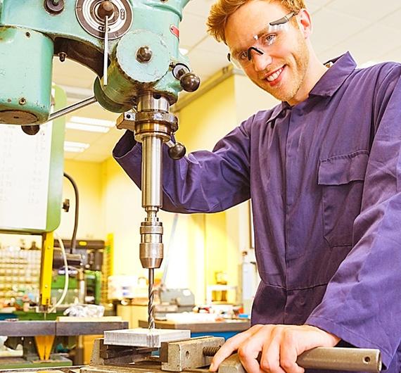 Lehrling steht an einer Bohrmaschine und trägt eine Schutzbrille und Handschuhe. Er bohrt ein Metall.
