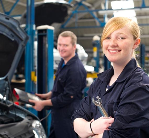 Ein blondes Mädchen steht in Arbeitskleidung mit Schraubschlüssel in der Hand in einer Werkstatt. Dahinter sind ein Mann in Abeitskleidung und ein Auto zu sehen.